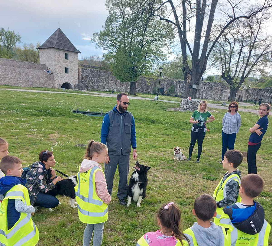 djeca stoje u krugu i gledaju pse i čovjeka koji stoji i priča