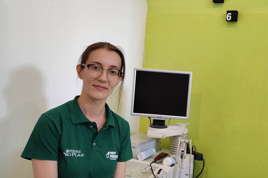 žena u zelenoj majici sjedi u veterinarskoj ambulanti