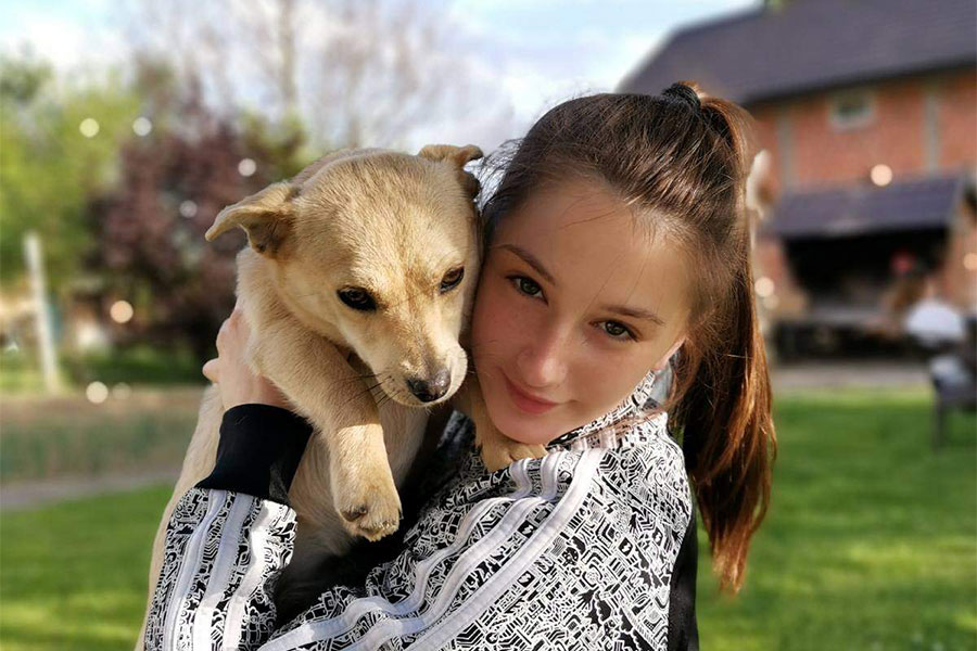 Djevojčica Anđela Stojić drži malog žutog psa